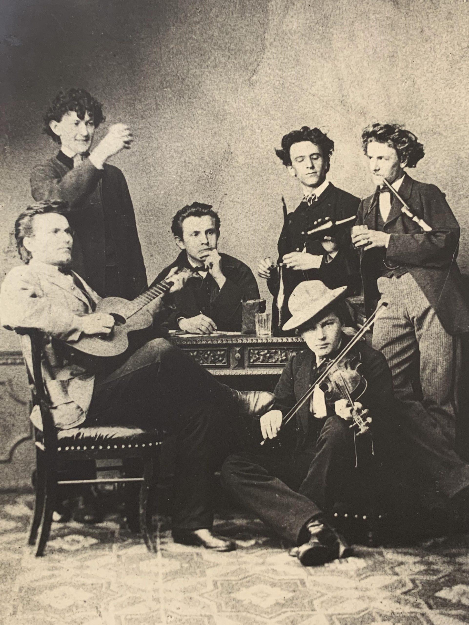 Jirásek (sedící, zadumaný) s Bohdanem Jelínkem (připíjející) a kamarády